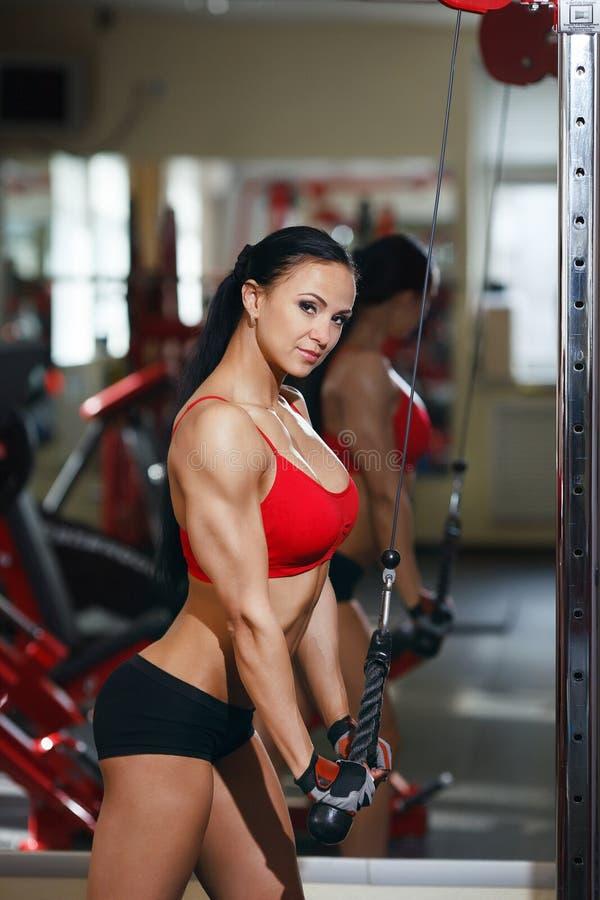 Девушка в спортзале делая трицепс работает на exerciser блока стоковые изображения