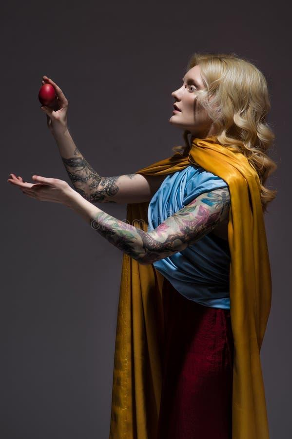 Девушка в средневековых красивых платье и пасхальном яйце стоковая фотография rf