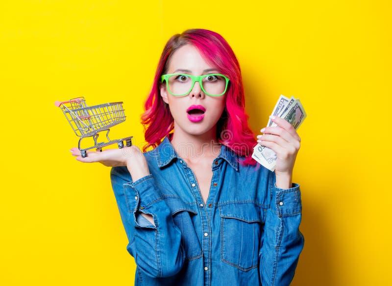 Девушка в стеклах держа магазинную тележкау и деньги стоковое изображение rf