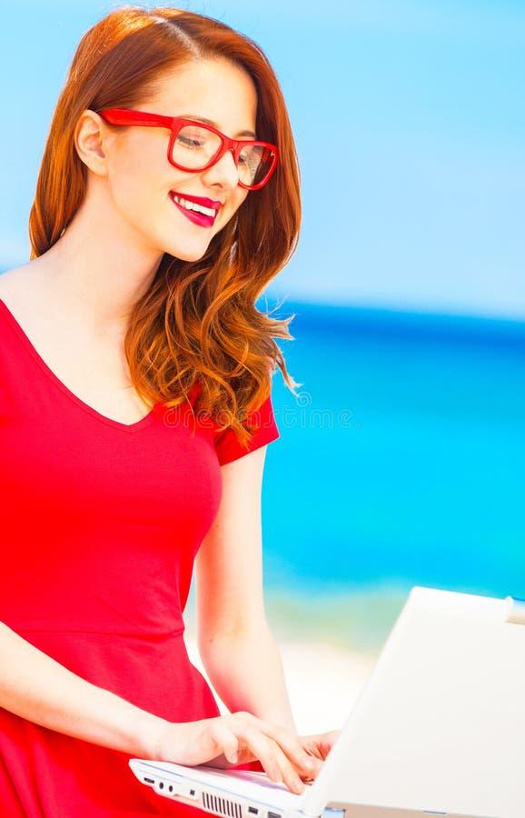 Девушка в стеклах с тетрадью на пляже стоковое фото