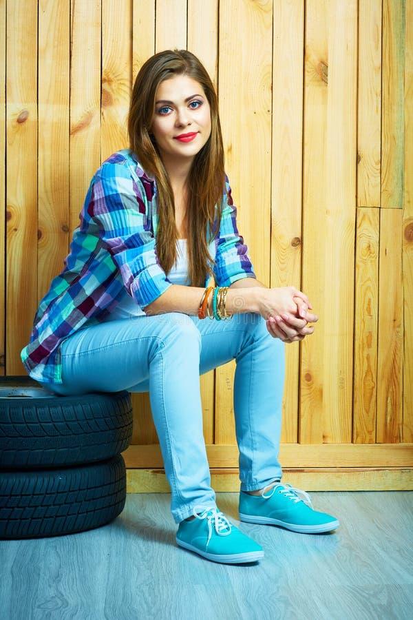 Девушка в стиле страны сидя на автоматических автошинах против желтой древесины стоковые изображения rf
