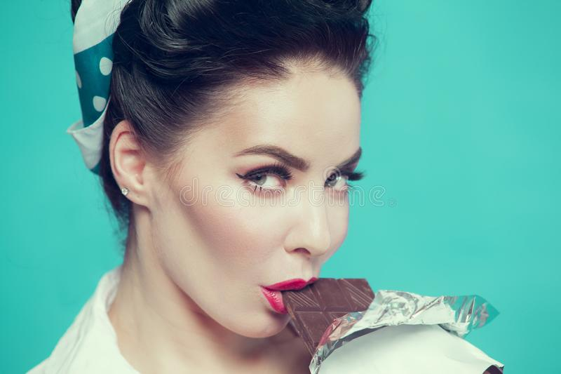 Девушка в стиле штыря-вверх сдерживая шоколадный батончик на голубой предпосылке стоковая фотография
