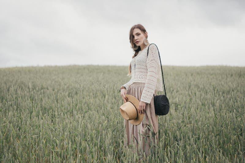 Девушка в стиле eco одевает представлять в предпосылке природы Портрет молодой женщины в шляпе boho Милый незнакомец ethno в поле стоковая фотография rf