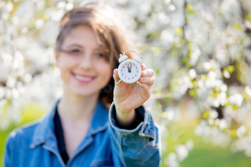 Девушка в стойках джинсовой ткани куртки и будильника около цветя дерева стоковые изображения rf