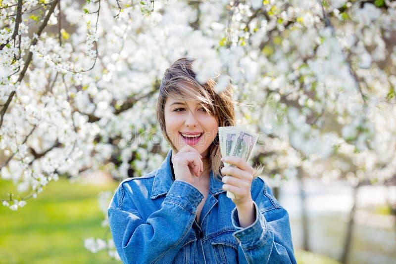Девушка в стойках джинсовой ткани куртки и денег около цветя дерева стоковое фото