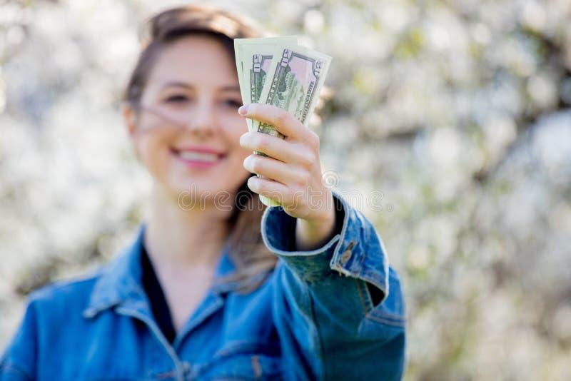 Девушка в стойках джинсовой ткани куртки и денег около цветя дерева стоковые фотографии rf