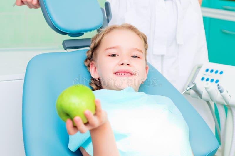 Девушка в стуле дантиста показывает зеленое яблоко стоковые изображения rf
