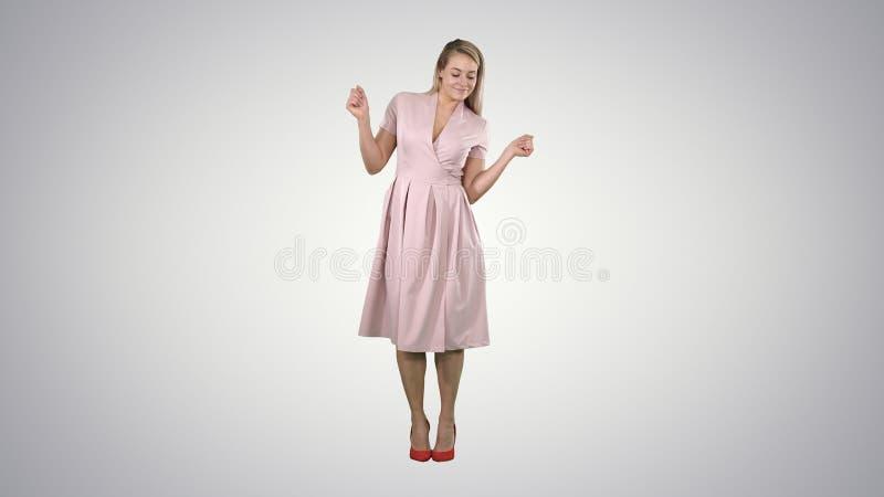 Девушка в танцах платья лета к музыке на предпосылке градиента стоковые фотографии rf