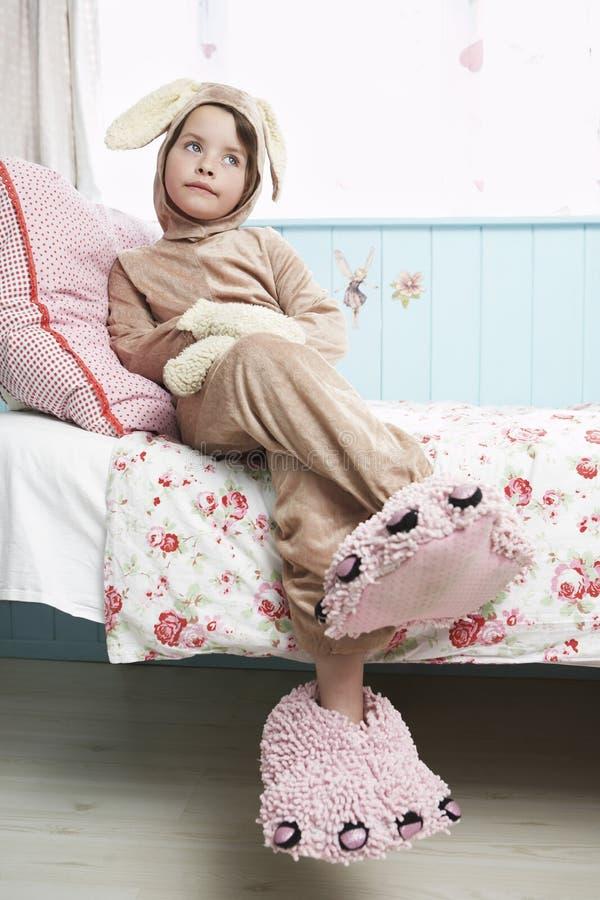 Девушка в тапочках костюма и изверга зайчика сидя на кровати стоковые изображения rf