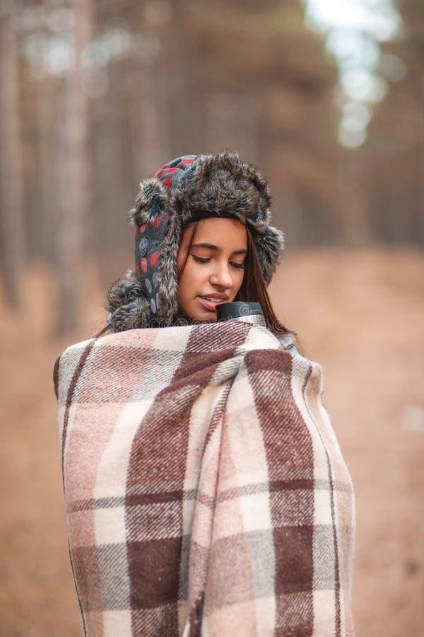 Девушка в теплой шляпе, предусматриванной в коричневой checkered шотландке, выпивая чай в лесе осени стоковая фотография rf