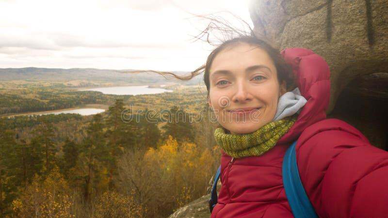 Девушка в теплых одеждах с шарфом с рюкзаком поверх массы утеса делает selfie на предпосылке природы осени стоковая фотография