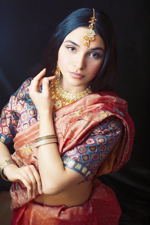 Девушка в усмехаться сари жизнерадостный, ювелирные изделия светя, концепция красоты сладкая реальная индийская людей образа жизн стоковая фотография