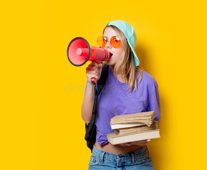 Девушка в фиолетовых одеждах с розовыми мегафоном и книгами стоковое фото rf