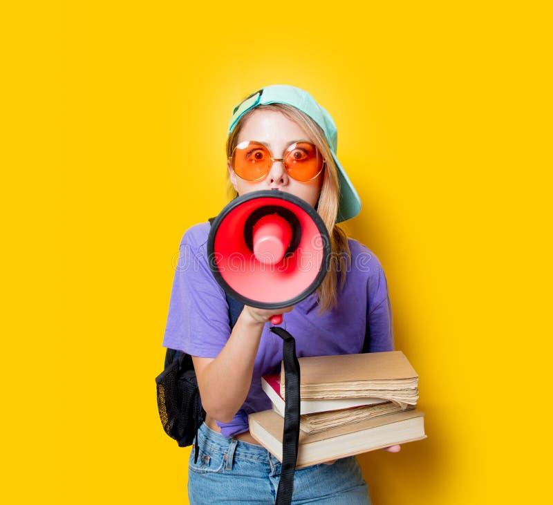 Девушка в фиолетовых одеждах с розовыми мегафоном и книгами стоковая фотография rf