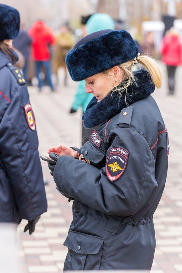 девушка в форме полиции зимы стоит на улице и смотрит смартфон стоковое фото rf