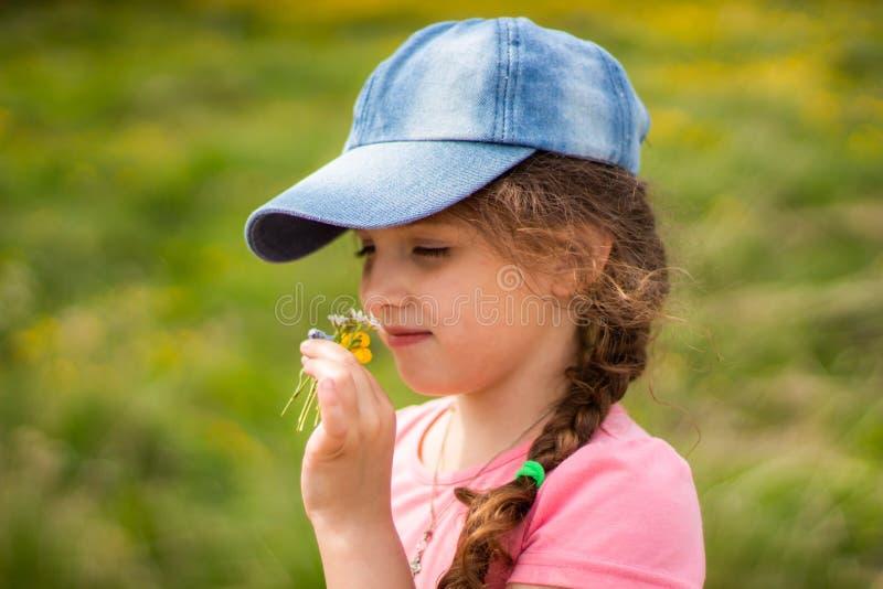 Девушка в цветках обнюхивать крышки в летнем дне стоковая фотография rf