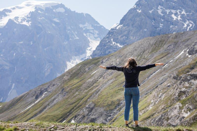 Девушка в ценах соломенной шляпы наверху горы и взглядах afar на облаках стоковые изображения rf