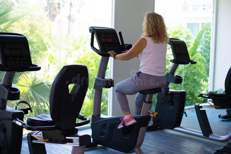 Девушка в черной носке спорта энергично работает на велотренажере стоковое изображение rf