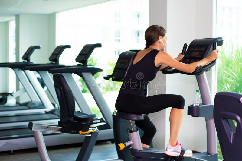 Девушка в черной носке спорта энергично работает на велотренажере, заднем взгляде стоковые изображения rf