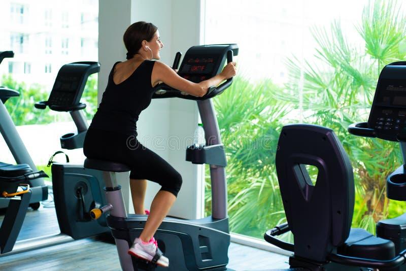 Девушка в черной носке спорта энергично работает на велотренажере, заднем взгляде стоковое изображение