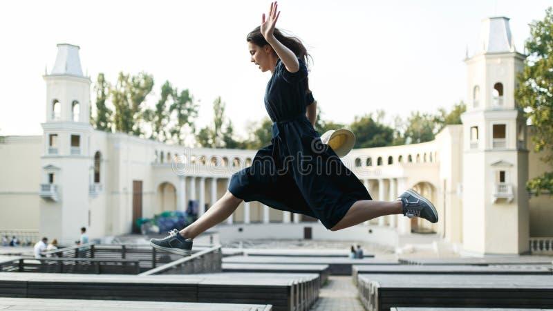 Девушка в черном платье скача на город стоковые фотографии rf