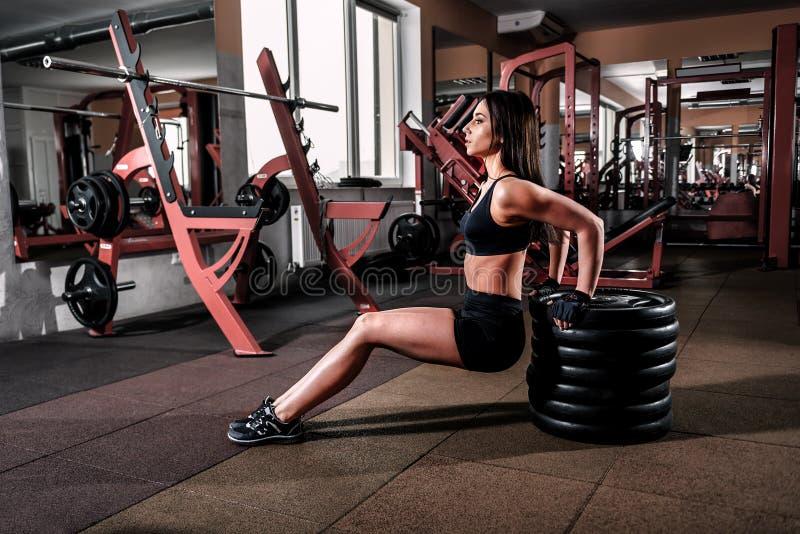 Девушка в черном платье спорта в спортзале стоковые изображения rf