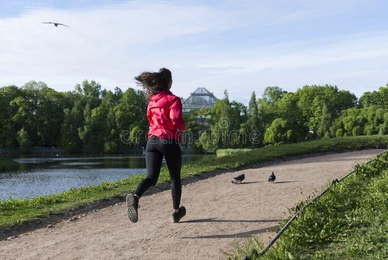 Девушка в черных гетры и красной куртке бежать вниз с пути в парке стоковые фотографии rf