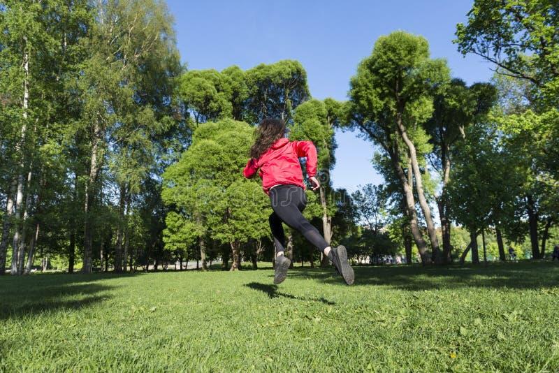 Девушка в черных гетры и красной куртке бежать через предпосылку луга зеленых деревьев и голубого неба, бегуна стоковые изображения rf