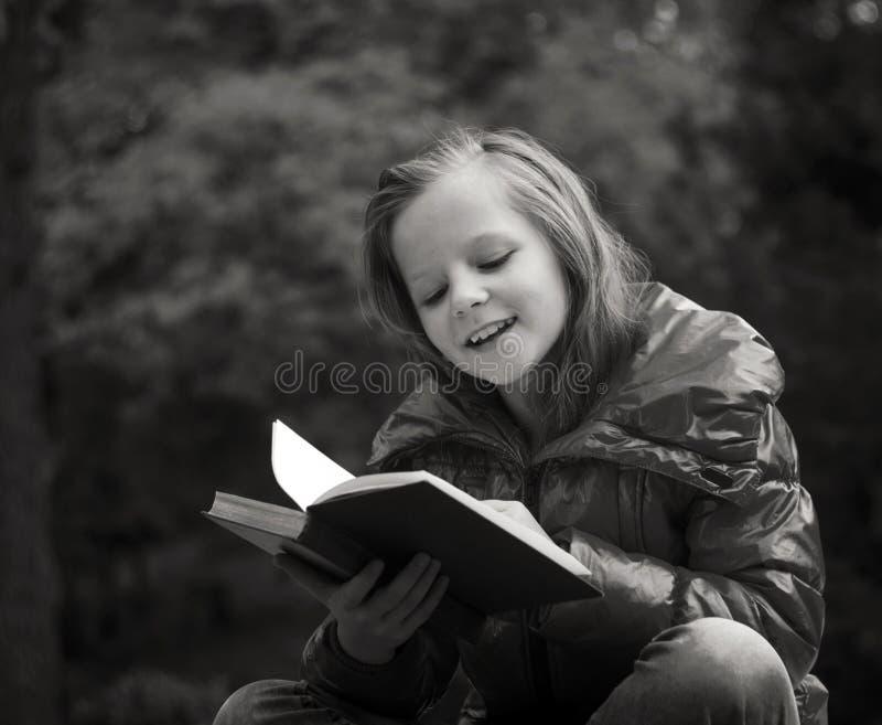 Девушка в чтении парка стоковое изображение rf