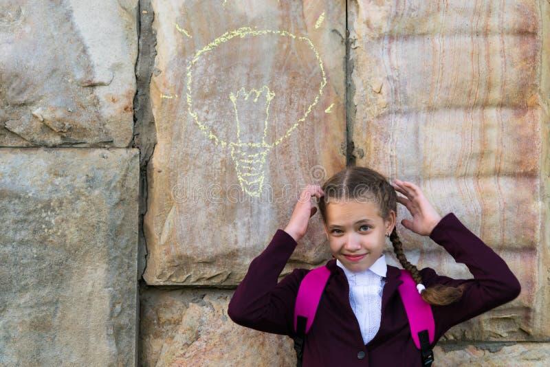 Девушка в школьной форме думает на предпосылке каменной стены на которой покрашена электрическая лампочка стоковое изображение rf