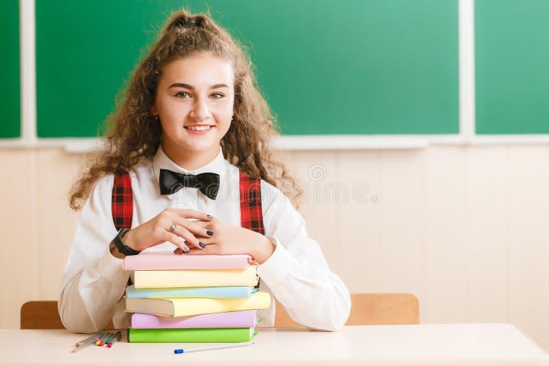 Девушка в школьной форме сидя на ее столе в классе с книгами Студент в классе в школе стоковые фотографии rf