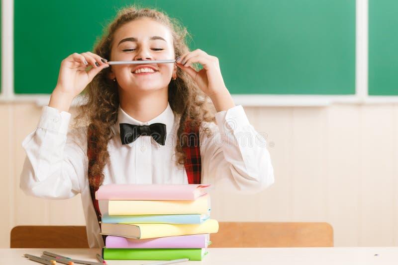 Девушка в школьной форме сидя на ее столе в классе с книгами Студент в классе в школе стоковое изображение rf