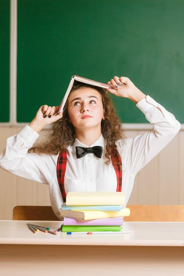 Девушка в школьной форме сидя на ее столе в классе с книгами Студент в классе в школе стоковые изображения rf