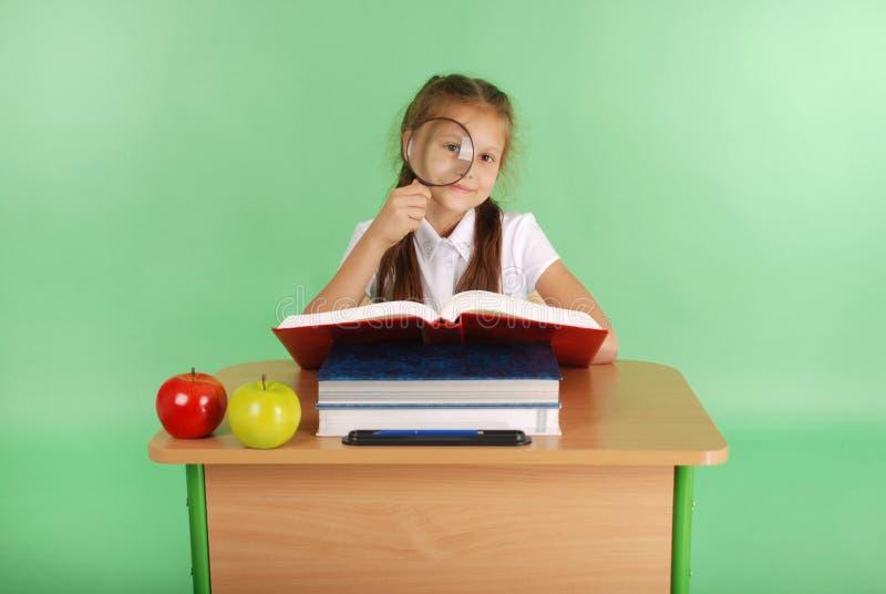 Девушка в школьной форме сидя на столе с лупой стоковые изображения rf