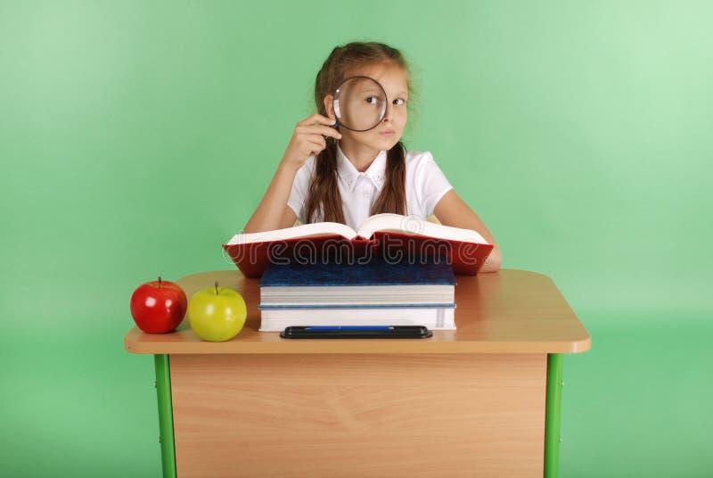 Девушка в школьной форме сидя на столе с лупой стоковые фото