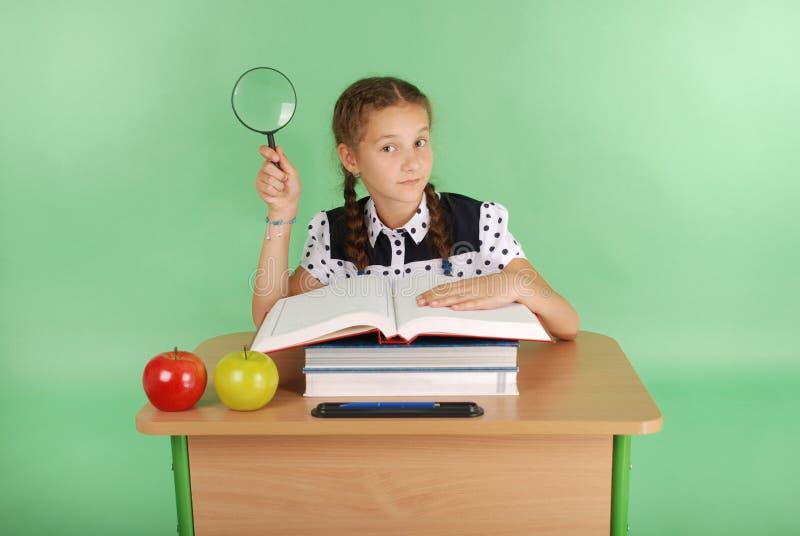 Девушка в школьной форме сидя на столе с лупой стоковое изображение