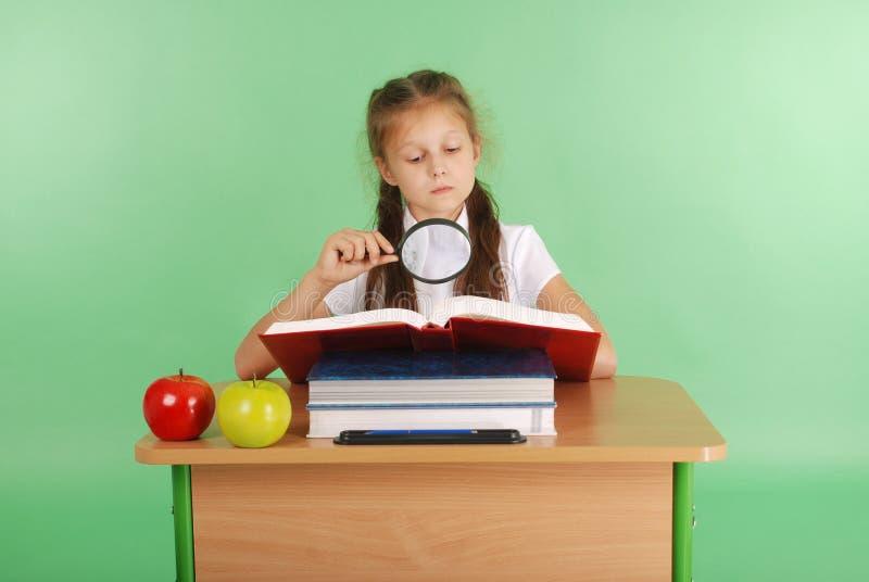 Девушка в школьной форме сидя на столе с лупой стоковая фотография