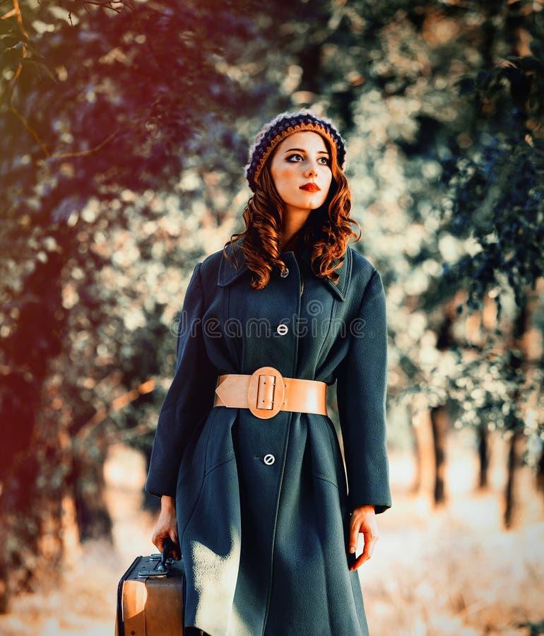 Девушка в шляпе и пальто с чемоданом на countyside стоковая фотография rf