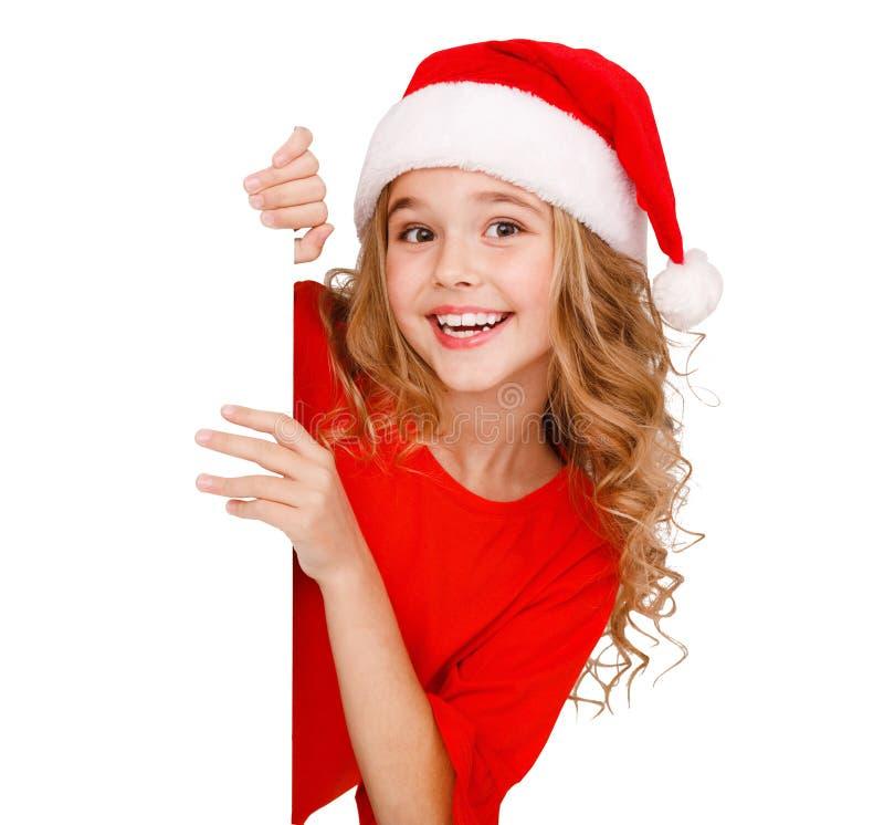 Девушка в шляпе santa, за белой панелью изолированной на белизне стоковая фотография