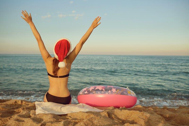 Девушка в шляпе santa на пляже морем на Рождество стоковые изображения