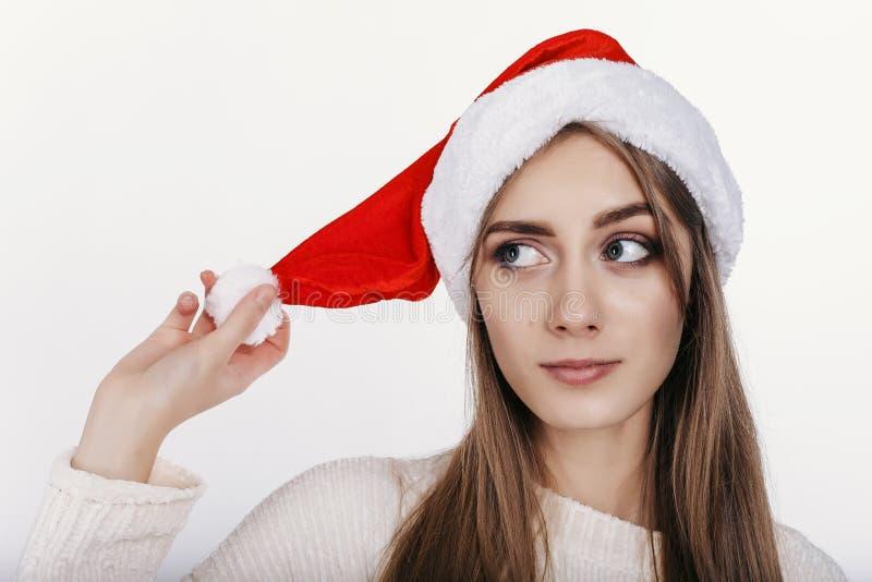 Девушка в шляпе santa смотря косой и думать стоковые фотографии rf