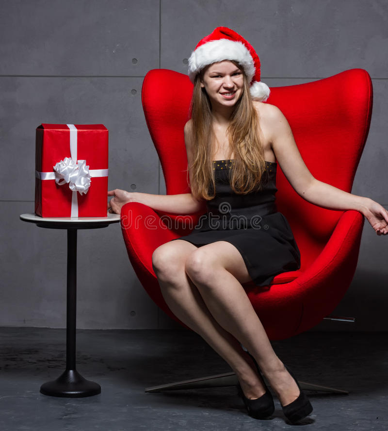 Девушка в шляпе Санта Клауса на подарках рождества стоковое изображение