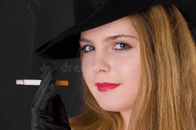 Девушка в шляпе с сигаретой стоковая фотография