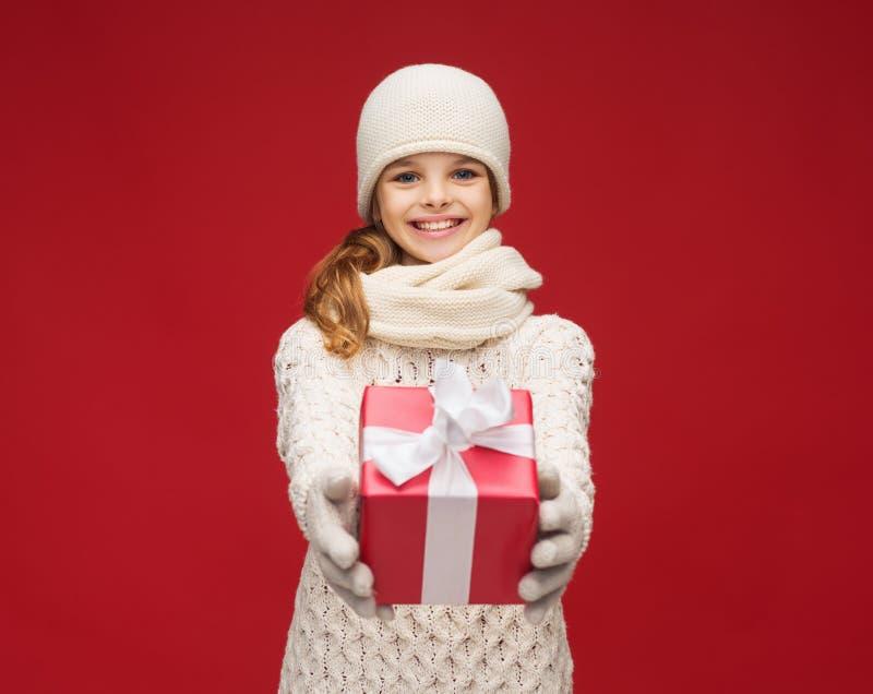 Девушка в шляпе, шумоглушителе и перчатках с подарочной коробкой стоковое изображение rf