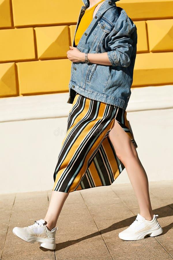Девушка в юбке и прогулках белых тапок уверенно через город, держа куртку джинсовой ткани Образ жизни улицы стоковое изображение rf