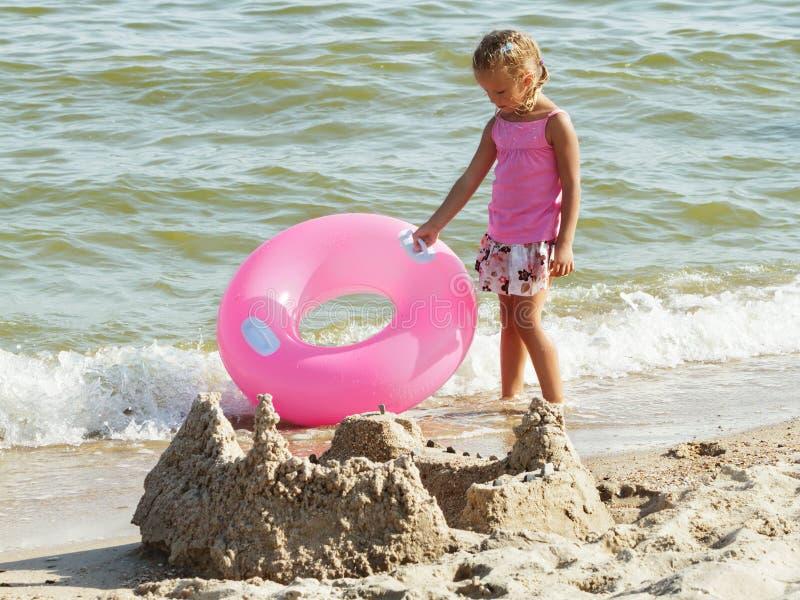Девушка в юбке с дети lifebuoy на пляже стоковая фотография