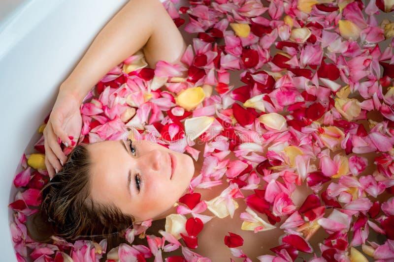 Девушка в bathroom с лепестками розы, закрывает вверх по портрету стоковое фото rf