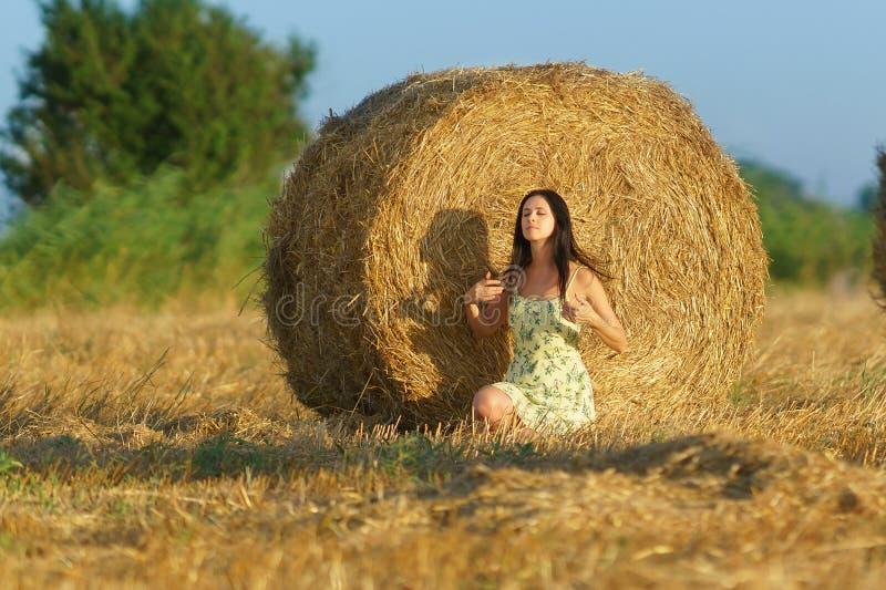 Девушка в sundress сидя вокруг связок соломы стоковое фото rf