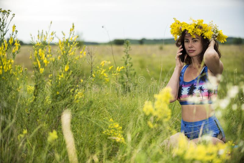 Девушка говорит телефоном на луге 2018 цветка стоковое фото rf