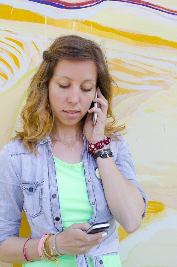 Девушка говоря на одном телефоне пока читающ текстовое сообщение стоковое фото